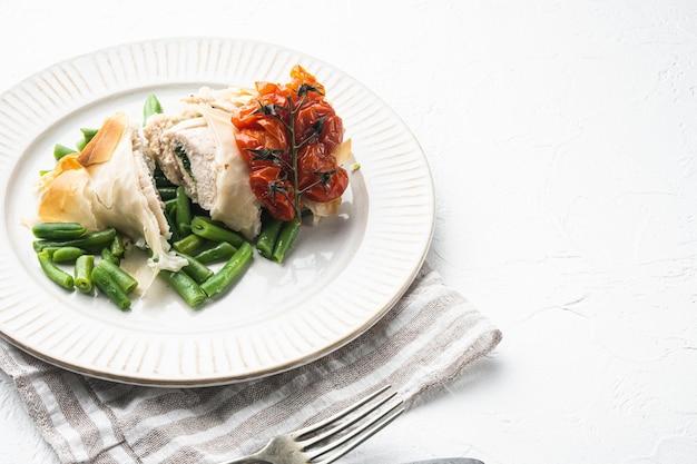 Viande de poulet farcie avec filo, avec tomates cerises au four et haricots verts, sur fond de pierre blanche, avec espace de copie pour le texte