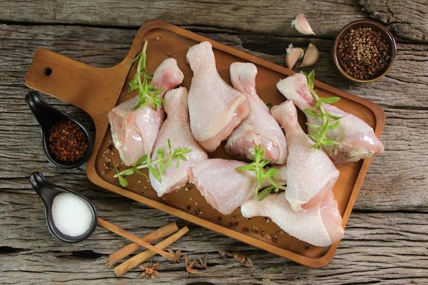 Viande de poulet fraîche au romarin et épices sur planche de bois.