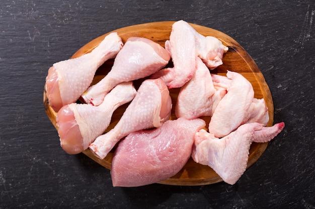 Viande de poulet fraîche sur tableau noir, vue du dessus
