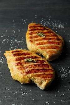 Viande de poulet grillé et sel sur fond de bois foncé