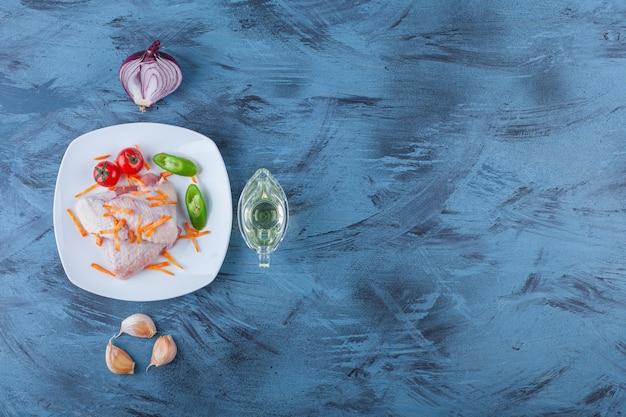 Viande de poulet et légumes sur une assiette à côté du bol d'huile, sur le fond bleu.