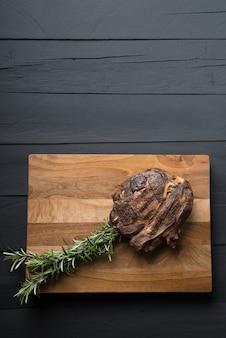 Viande rôtie sur une planche à découper sur un fond en bois noir