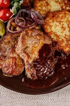 Viande en sauce avec garniture sur une assiette.