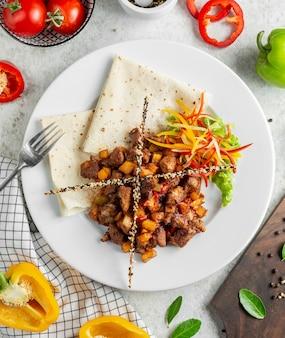 Viande sautée servie avec salade fraîche de pain plat et bâtonnets de pain