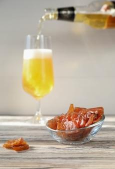 Viande séchée avec une bouteille de bière et un verre