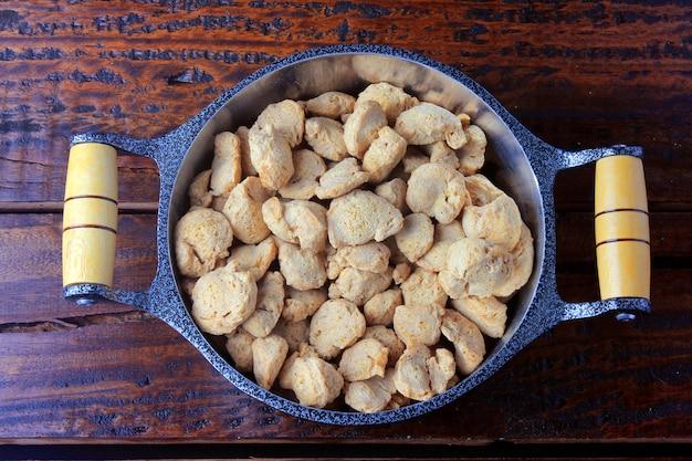 Viande de soja, morceaux dans une casserole rustique. vue de dessus des morceaux de soja crus sur fond en bois rustique