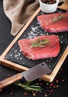 Viande de steak de boeuf cru frais sur planche de cuisine en pierre avec hache et poivre