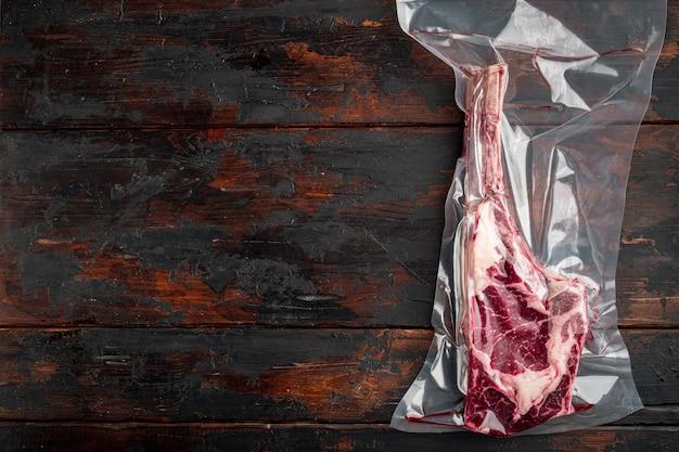 Viande De Steak De Boeuf Tomahawk Cru Frais Et Sec Dans Un Emballage Sous Vide En Plastique, Sur La Vieille Table En Bois Sombre, Vue De Dessus à Plat Photo Premium