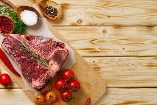 Viande de t-bone crue avec des légumes frais et du romarin sur la table