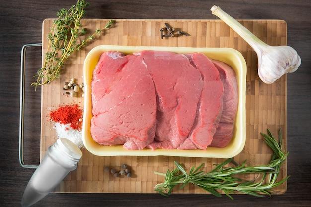 Viande de veau fraîche et crue steaks avec assaisonnements d'affilée prêts à cuire