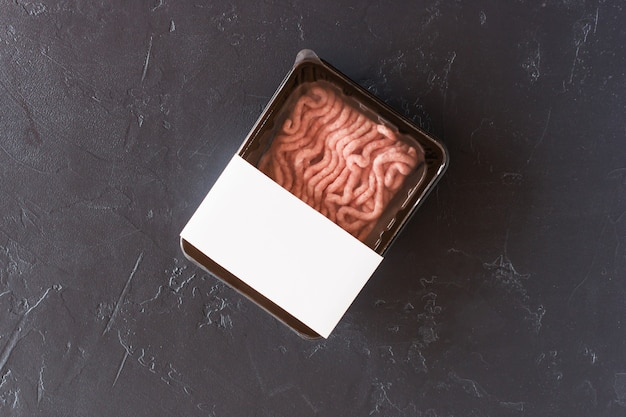 Viande de volaille hachée fraîche dans un emballage sous vide. produit semi-fini. vue de dessus. maquette de logo pour la conception.