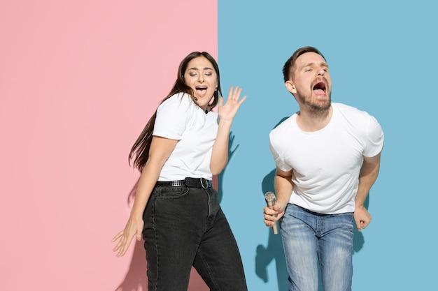 Vibrations. danser, chanter, s'amuser. jeune et heureux homme et femme en vêtements décontractés sur un mur bicolore rose et bleu. concept d'émotions humaines, d'expression faciale, de relations, d'annonce. beau couple.