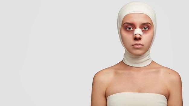 Une victime de beauté dans des bandages médicaux a un autocollant sur l'arête du nez a des ecchymoses après l'opération