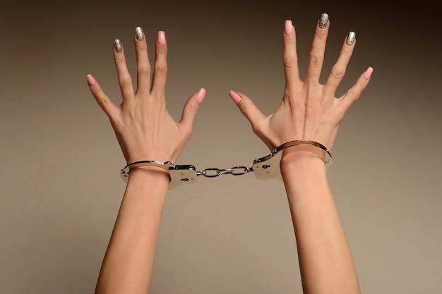 Victime du concept de mode avec des mains féminines menottes aux poignets