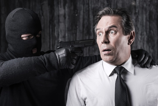 Victime de violences. homme d'affaires choqué attrapé par un criminel visant sa tête avec une arme à feu