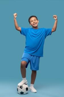 La victoire. heureux garçon à la peau foncée en vêtements de sport bleus avec ballon de football levant les mains victorieusement