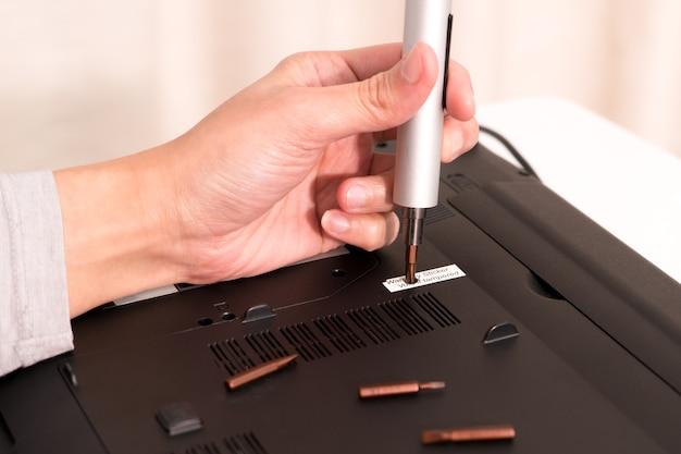 Le vide de la garantie après que les femmes réparent un ordinateur portable en utilisant un tournevis, une réparation et un entretien