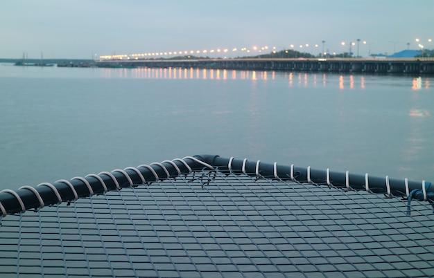 Vide lit hamac sur l'eau avec pont de la mer floue en toile de fond
