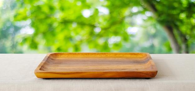 Vide plateau en bois carré sur fond de parc vert flou.