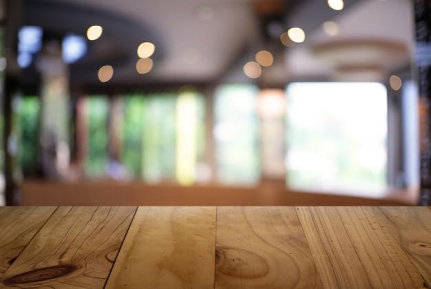 Vide table en bois sombre en face de l'arrière-plan flou abstrait du café-restaurant. peut être utilisé pour l'affichage ou le montage de vos produits.mock up pour l'affichage du produit