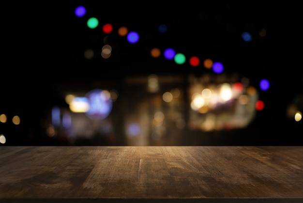 Vide de table de bois sombre en face de l'arrière-plan flou abstraite de la lumière bokeh. peut être utilisé pour l'affichage ou le montage de vos produits.moteur pour l'affichage du produit