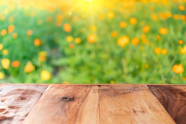 Vide vieille planche de bois sur le champ de fleurs nature flou pour montrer le produit.