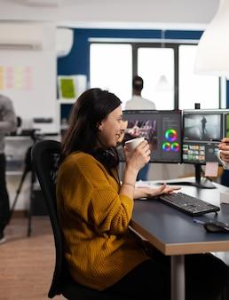 Une vidéaste appréciée éditant un projet vidéo buvant du café à l'aide d'un logiciel de post-production travaillant dans une entreprise multimédia numérique avec deux moniteurs