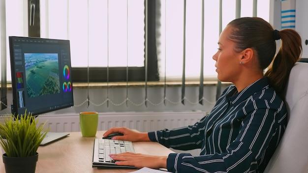 Vidéaste hispanique indépendant éditant un nouveau projet travaillant dans une entreprise moderne créant du contenu. entrepreneur dans l'écriture d'un espace de travail professionnel sur un clavier d'ordinateur en regardant le bureau
