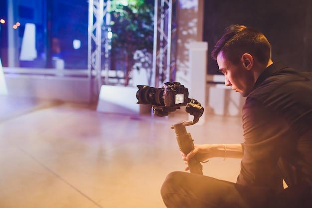 Vidéaste professionnel tenant la caméra sur un cardan 3 axes. vidéaste utilisant steadicam. l'équipement pro permet de réaliser des vidéos de haute qualité sans trembler.
