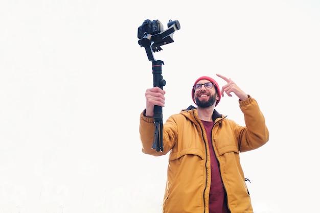 Vidéaste se filmant avec un appareil photo reflex numérique sur un cardan motorisé