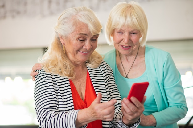 Vidéo intéressante. deux femmes âgées regardant quelque chose sur un smartphone