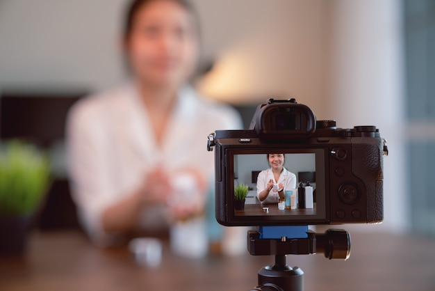 Une vidéo de vlogger beauté jeune femme asiatique en ligne montre le maquillage des produits cosmétiques et une vidéo en direct sur un appareil photo numérique.