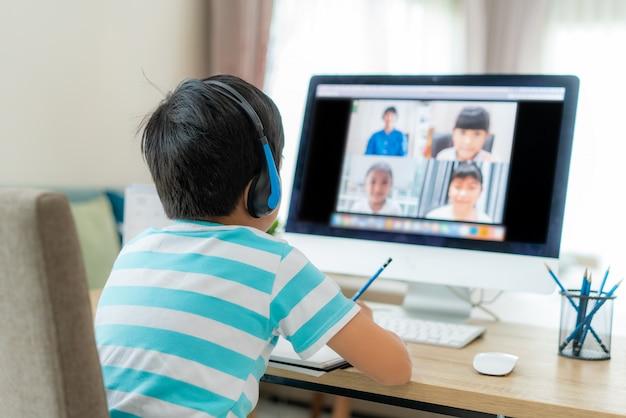 Vidéoconférence d'un étudiant asiatique avec un enseignant et des camarades de classe sur ordinateur