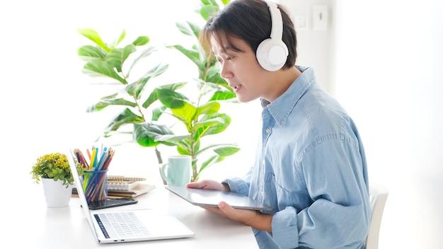 Vidéoconférence travail à domicile homme asiatique faisant un appel vidéo à une équipe commerciale avec un site web virtuel