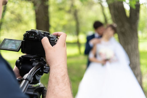 Le vidéographe tourne les mariés dans le jardin en été.