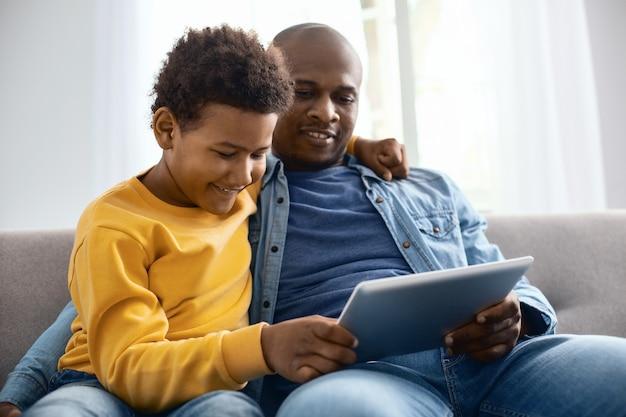 Vidéos intéressantes. joyeux garçon pré-adolescent étreignant son père et regardant des vidéos avec lui tout en vous relaxant sur un canapé