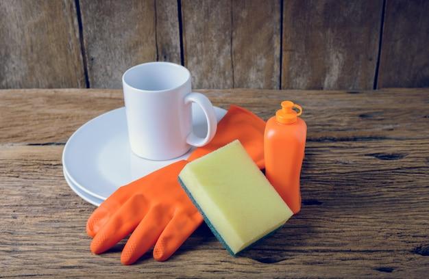 Vider les assiettes et la tasse avec du liquide vaisselle, des éponges et des gants en caoutchouc