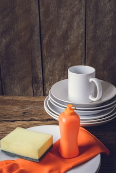 Vider les assiettes et la tasse avec le liquide vaisselle, les éponges et les gants en caoutchouc
