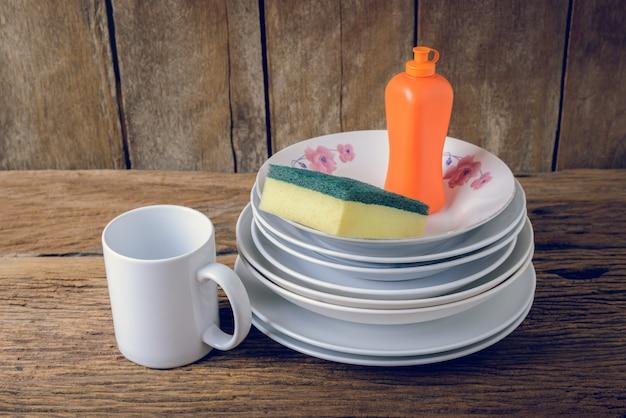 Vider les assiettes et la tasse avec le liquide vaisselle, les éponges