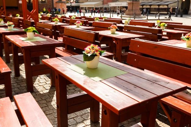 Vider les grandes tables et bancs en bois sur des pavés dans un café de la vieille ville