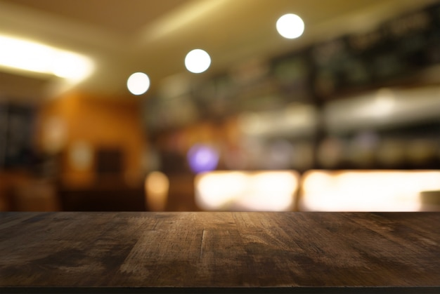 Vider la table en bois sombre en face d'un fond abimé en flou de l'intérieur du café et du café. peut être utilisé pour l'affichage ou le montage de vos produits.