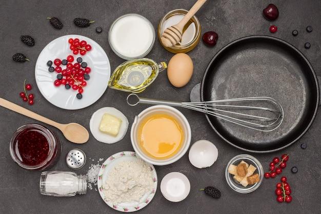 Videz la casserole et fouettez. farine, œufs cassés, lait de baies, beurre, confiture de miel. ingrédients pour préparer le petit-déjeuner. mise à plat