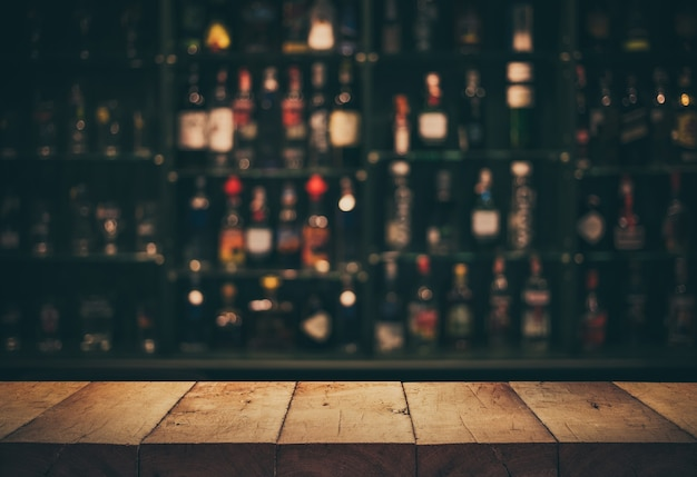 Videz le haut de la table en bois avec un comptoir flou et des bouteilles