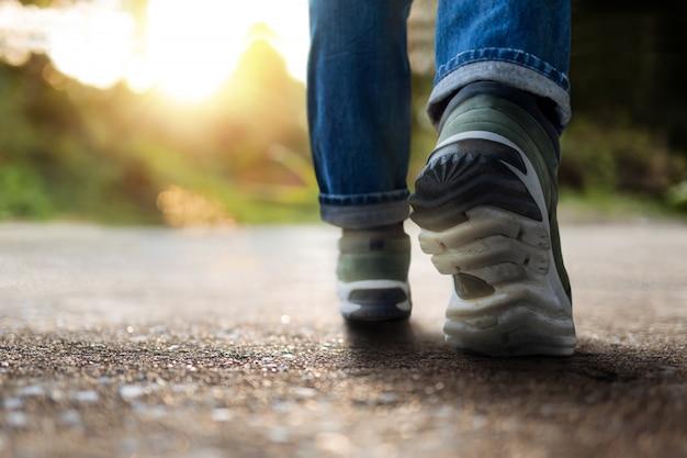Vie et concept stimulant. section basse du jeune homme motivé, marcher en plein air. lumière naturelle du soleil