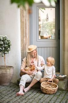 La vie du village. country boy avec papa poulet brun et un grand panier dans la cour près de la porte d'entrée