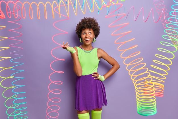 La vie est lumineuse. une femme afro-américaine positive se refroidit à l'intérieur et s'amuse à une soirée disco