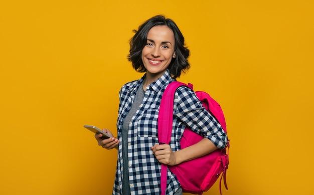 La vie d'étudiant! une belle jeune étudiante, habillée avec désinvolture, avec son joli sac à dos rose sur une épaule, regardant avec un large sourire, tenant son smartphone dans sa main.