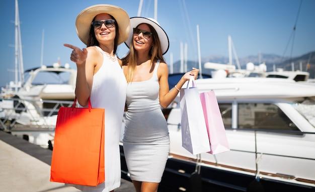 Vie luxueuse pour deux femmes marchant et faisant du shopping en vacances