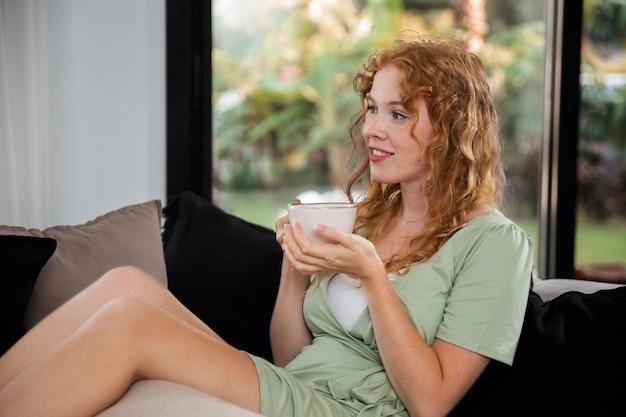 La vie à la maison avec un jeune adulte buvant une boisson chaude