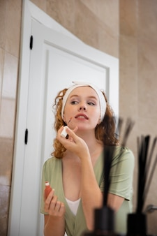 La vie à la maison avec un jeune adulte qui nettoie son visage
